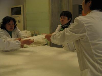 Kiinalaiset valmistavat silkkipeittoa käsityönä.