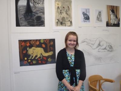 suvun nuorin taiteilija Elina Lattu maalaamiensa taulujen edessä. Elina lauloi myös heleällä äänellään avajaisvieraiden iloksi.