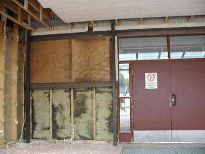 Märkiä ja mustuneita eristeitä on löytynyt koulun seinistä runsaasti. Kuva pääovelta.