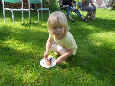 Tässä kuvassa kurssin pienin, Matilda mustikkapiirakkansa kanssa nurmikolla pienellä piknikillä.