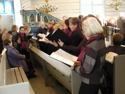 Seurakunnan lauluryhmä esiintyi kirkon penkissä ehtoollisen aikaan.