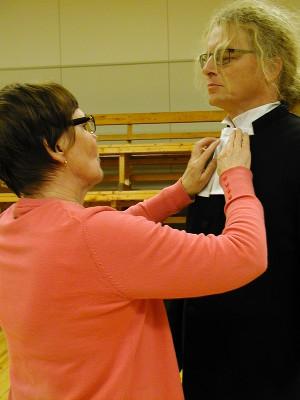 Airi Peutere kiinnitti lipereitä Arto Heimosen kaulaan. Liperit ja papinpuku ovat lainassa emerituskirkkoherra Lauri Vaalgamaalta.