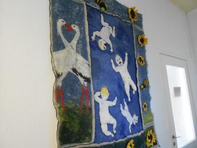 Asuintilaan johtavalla käytävällä on suuri huovutustyö, sinisellä pohjalla pulleita vauvoja.