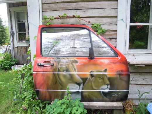 Mikko Loisan auton oveen maalaamat leijonat vartioivat Mänyuperän pihamaata.