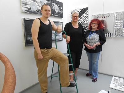 Ripustuspäivänä paikalla olleet taiteilijat vasemmalta Jasu Rouhiainen, Maarit Vepsä (taustalla hänen taulunsa) ja Pirjo Martikainen.