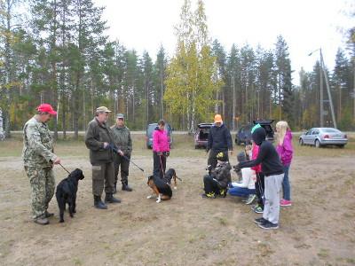 Urheilukentällä oli Eetu Laarin vetämä koirapiste, jossa ryhmä oppilaita sai tutustua metsästyskoiriin, vasemmalla sileäkarvainen noutaja, sitten kaksi suomenajokoiraa ja harmaahirvikoira.