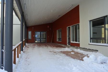 Talon sisäänkäynti Palolankujan puolella, missä on tilaa myös vierailijoiden autoille.