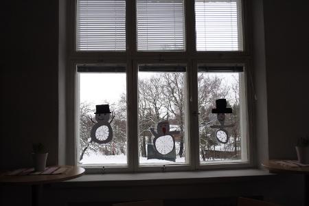 Ekaluokkalaisten lumiukot kurkkivat ikkunoista kevään edistymistä.