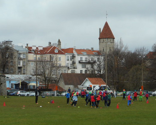 Koululaiset viettivät ulkolilutuntia pelaillen ja palloa potkien kaupungin muurien edessä.