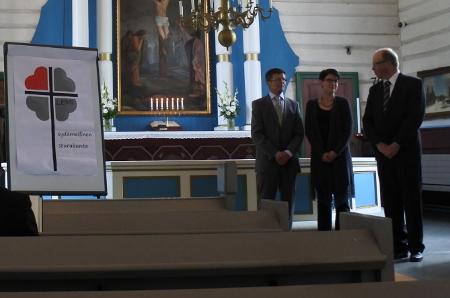 """Juhlassa paljastettiin Kaisa Vainikan suunnittelema seurakunnan logo tekstillä """"Lemi - sydämellinen seurakunta"""". Martti Räty ja Kari Haiko saivat kiitokset puusepäntöistään, joille he ovat kirkkoa kohentaneet,"""