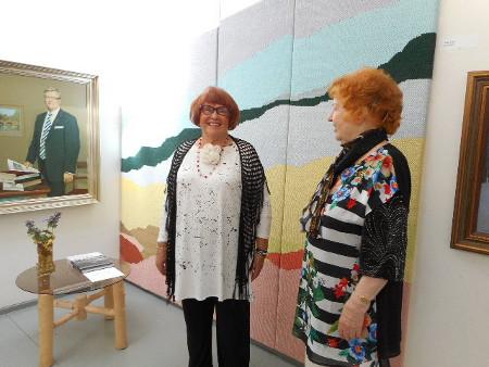 Tässä muotokuvahuoneessa Anneli Jaakkola ja Eeva Jokipelto Aino Uskin kookkaan seinävaatteen edessa.
