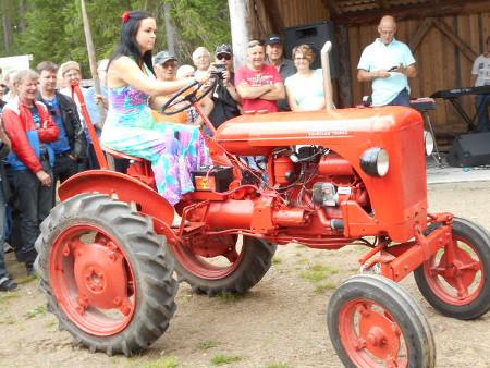 Tässä kuvassa hän nostelee helmansa punaiseen kulkupeliin, ja eikös vain valmiiksi käynnistetty traktori lähtee varmasti liikkeelle.