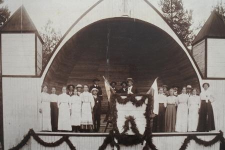Arci Tawastin ottamassa valokuvassa noin vuodelta 1910 juhlitaan ensimmäisen laululavan valmistumista. Kuoroa johtaa Evert Korttinen. Kuva on Taikalyhdyn kokoelmista.