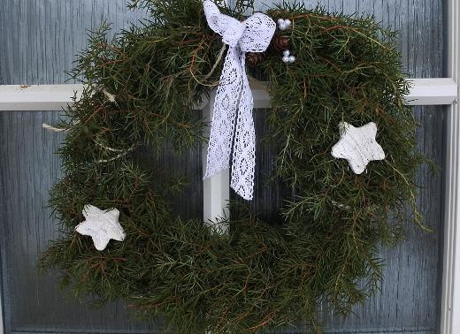 Kranssit ovella toivottavat hyvää joulua.