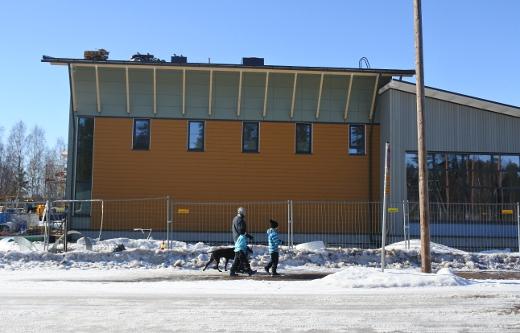 Koulu Juvolantien puolelta nähtynä. Liikuntasalin ukkoseinien väritys muistuttaa Lemin kirkosta, muu osa on samaa siniharmaata kuin vastapäinen päiväkoti.