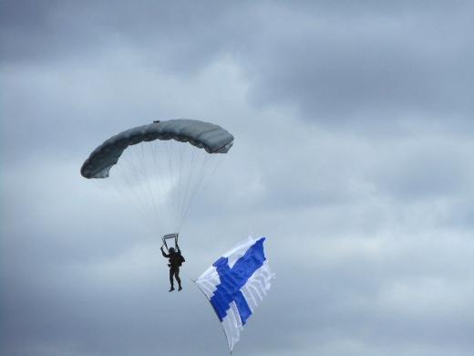 Laskuvarjohyppääjä toi kauniisti hulmuavan Suomen lipun kentälle.