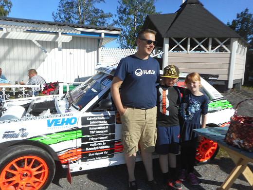ralliauton edessä poseeraavat vas. Toni Kuhanen, Lari Kuhanen ja Sara Ruhanen.