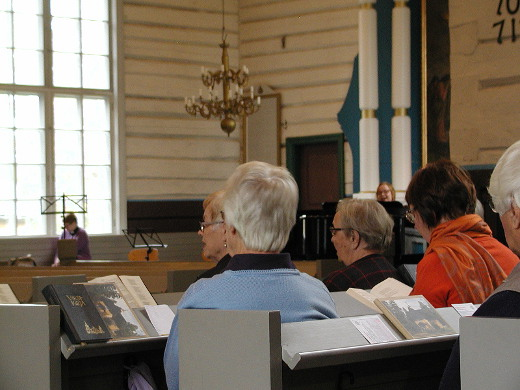 Lemin kirkkokuoro istui alhaalla kirkkosalissa antamassa esimerkkiä. Kanttori Jonna Imeläinen säesti.