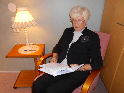Hely Hyrkkänen, 81, istuu lukulampun alla ja lukee muutamia runoja upouudesta runokirjastaan .