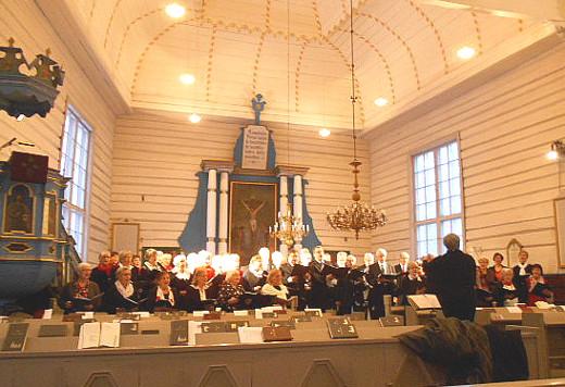 Kolme kirkkokuoroa liitettiin konsertissa suurkuoroksi. Kuvassa se esiintyy Taipalsaaren kanttorin Tea Lavasten johdolla.