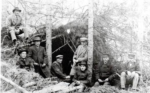 Lemin punaista miehitystä paenneita valkoisia metsässä havumajan suojassa, oik. kunnan esimies Antti Okko ja kauppias Aatu Pekari.