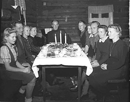 Joulupöytä Klemin kantatalossa, Klemin perhe 1944. Vasemmalta Kaija, isäntä Toivo, emäntä Anna-Liisa, vanhaemäntä Regina Klemi. Pöydän päässä konstaapeli Heimo Klemi Pöydän oikealla puolella talon pojat Paavo ja Reino sekä tyttäret Marjatta.. Kuva Eino Suonio/Taikalyhty