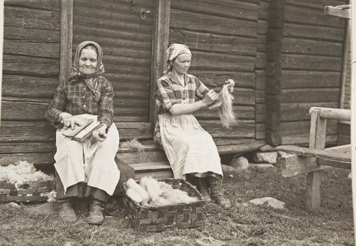 Tyyni Vahterin valokuva vuodelta 1929 on yksi niistä. Kuvassa vanhaemäntä  Kansikuva vanha emäntä Rikiina Klemi raasii villoja, valmiit ns. mökölöitä; miniänsä Annaliisa harjaa pellavia Vahter, Tyyni, kuvaaja 1929 Museovirasto